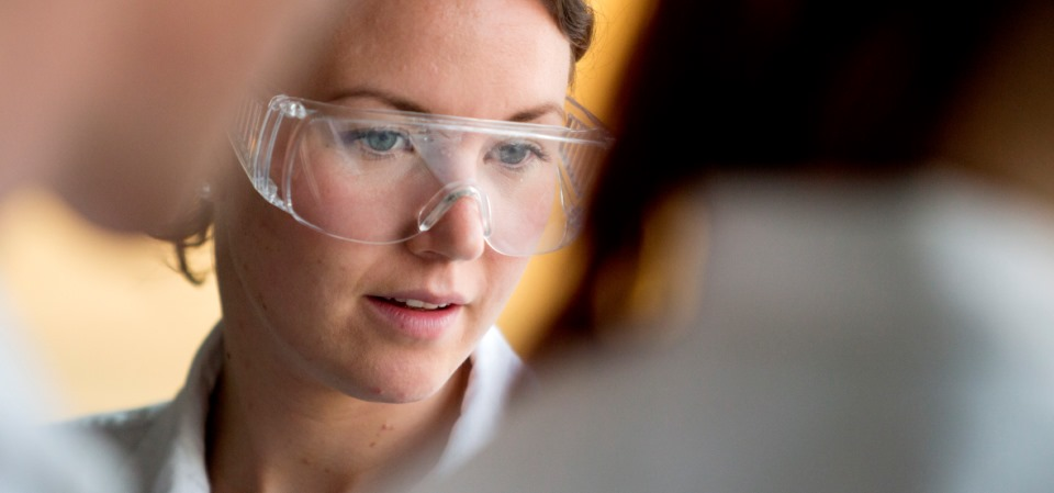 Chemistry student with laboratory skirt and safety goggles.