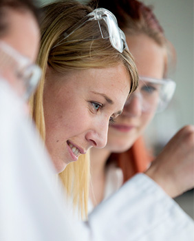 A couple of female chemistry students dressed in laboratory coats and safety goggles.